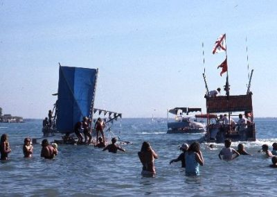 The beer can boats are off and racing. Spectator in the water watching the race 1985